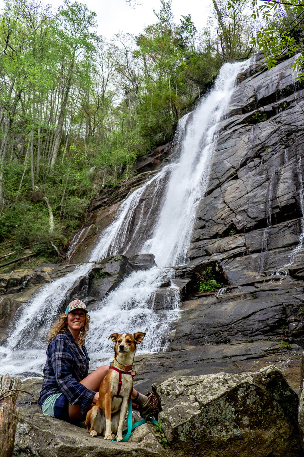 woman and dog in front of upper tier of falls creek falls